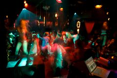 Dance Crowd in Motion. Purposely blurry slow sync dance crowd image with dj in nightclub royalty free stock images