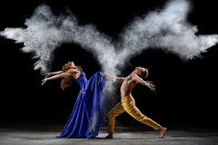 Dance duet with the powder mixtures in the dark. Dust clouds. blue and yellow costumes. Staging and exhibition photo stock photos