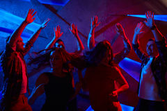 Dance enjoyment. Group of raving dancers enjoying discotheque Royalty Free Stock Images