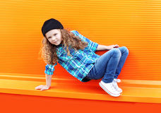 Dance and fashion kid concept - stylish little girl child. Wearing a shirt and cap dancing in the city against the colorful wall Royalty Free Stock Photo
