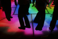 Dance floor. Colorfully lit dance floor, with human silhouettes in motion, dancing Stock Photo