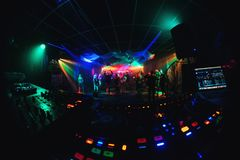 Dance floor and stage in night club with dancing crowd and DJ equipment and mixer. Dance floor and stage in the night club with a dancing crowd and DJ equipment Stock Photos