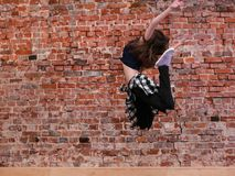 Dance is freedom. Happiness in moving. Lightness in life, sporty teenage girl on brick wall background with free space. Hip hop lifestyle, dancing young female stock image