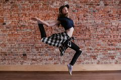 Dance is freedom. Lightness in life. Happiness in moving, sporty teenage girl on brick wall background with free space. Hip hop lifestyle, dancing young female stock images