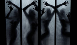 Dance of ghosts. Silhouette of the naked lady dancing behind the glass