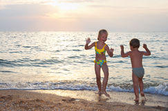 Dance in gold. Small girl and boy play and dance near evening sea Royalty Free Stock Photo