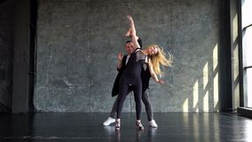 Dance on a gray background. professional couple dancers dancing professionally on a gray background. Slow-motion stock footage