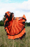 Dance of a gypsy girl. Gypsy girl in a gorgeous orange dress dances in a field Royalty Free Stock Photos