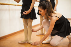 Dance instructor helping girls with posture Stock Photo