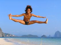 Dance jump on tropical beach. High dance, cheer dance or ballet jump by an acrobatic Asian teenager on a pristine exotic beach surrounded by tropical islands Royalty Free Stock Photos