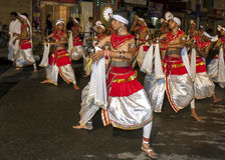 Dance of Kothala performers parade through the streets of Kandy during the Esala Perahera in Sri Lanka. Stock Photos