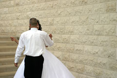 Dance with me to the end of love?. A bride and a groom next to a brick wall stock photo