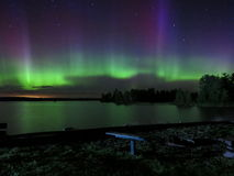 Dance of the Northern Lights. The Aurora Borealis shines, shimmers and dances its reflection over the calm waters of a northern Minnesota lake Royalty Free Stock Photos