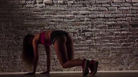 Dance o twerk com a menina energética no short contra uma parede de tijolo Movimento lento Fim acima vídeos de arquivo