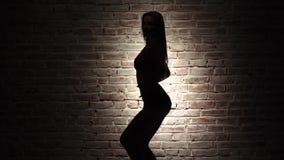 Dance o twerk com a menina no short de brim contra uma parede de tijolo Silhueta Movimento lento Fim acima vídeos de arquivo