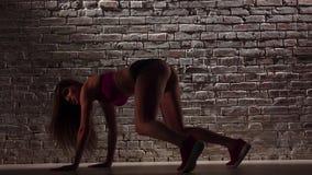 Dance o twerk com a mulher 'sexy' no short contra uma parede de tijolo Movimento lento Fim acima filme