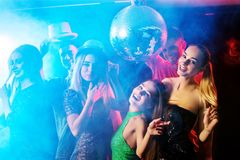 Dance party with group people dancing and disco ball. Dance party with group people dancing. Women and men have fun in night club. Back light on girls hair Royalty Free Stock Images