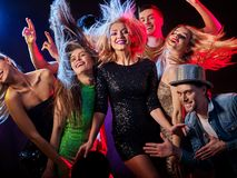 Dance party with group people dancing and disco ball. Dance party with group people dancing. Women and men have fun in night club. Happy girl with tousled hair Royalty Free Stock Images