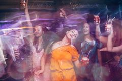 Dance party in night club in blurred motion. Happy friends at Christmas celebration, active New Year company, modern youth life Stock Image