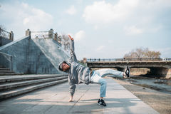 Dance performer, hip hop dancing  on the street. Modern dance style. Male dancer, cityscape on background Royalty Free Stock Photography