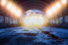 Dance place in abandoned hangar at night. Zombie dance place in abandoned ruined hangar with and blood on the floor and lots of lights in the green forest at Royalty Free Stock Images