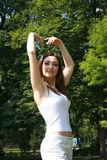 Dance pose. A young woman with long auburn hair stands with the hands gracefully over her head, in a ballet pose. She is standing in a park Stock Photography