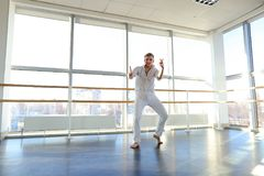 Dance school graduate making body movements. Graduate of dance school moves in white suit. Happy guy raving at gym. Concept of promotion to start dancing career Stock Photo