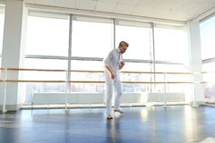 Dance school graduate making body movements. Graduate of dance school moves in white suit. Happy guy raving at gym. Concept of promotion to start dancing career Royalty Free Stock Photos