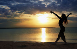 Dance at the sea. Elegant lady dancing sportive aerobics at the beach during sunset royalty free stock photography