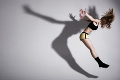 Dance with shadow. Dirl is jumping up with her shadow Stock Photography
