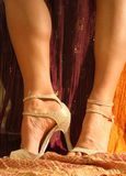 Dance shoes. Sexy legs wearing golden salsa shoes with glitter, high (90 mm) heels Royalty Free Stock Image