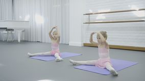 In dance studio two girls sit on mats and learn how to do movements. Little children in skirts attend training on ballet and synchronously repeat exercises stock video
