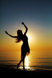Dance at Sunset. Girl dances on the beach at sunset. Natural light and darknesss. Artistic colors added. Vertical photo Stock Photos