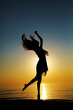 Dance at Sunset. Girl dances on the beach at sunset. Natural light and darknesss. Artistic colors added. Vertical photo Royalty Free Stock Photography