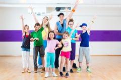 Dance teacher giving kids Zumba fitness class stock images