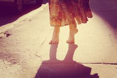 Dance on tiptoe. Girl is walking in the summer city. Sun is shining brightly royalty free stock image