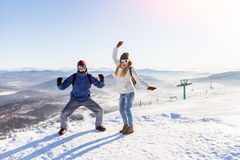 Dance on the top of a ski slope. Girl and guy in masks for snowboarding joyfully dancing on top of a mountain on the background of the ski slopes Royalty Free Stock Photo