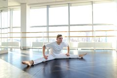 Dance trainer doing backwards close up somersault . Young dancer doing close up backwards somersault . Male person training at gym studio. Concept of stock photos
