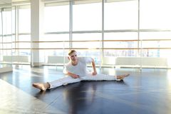 Dance trainer doing backwards close up somersault . Young dancer doing close up backwards somersault . Male person training at gym studio. Concept of royalty free stock photo