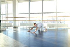 Dance trainer doing backwards close up somersault . Young dancer doing close up backwards somersault . Male person training at gym studio. Concept of royalty free stock image