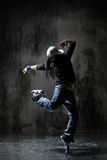 The dancer. Modern style dancer posing on dirty grunge background Stock Photography