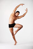 The dancer. Young male dancer posing over grey background stock photo