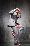 The dancer. Hip-hop style dancer posing on a grunge wall background Stock Photos
