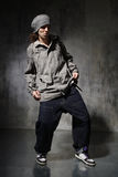 The dancer. Hip-hop style dancer posing on a grunge wall background Royalty Free Stock Images