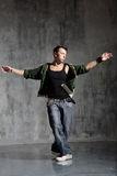 The dancer. Coll looking dancer posing on a grunge grey wall Stock Photography