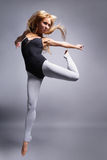 The dancer. Beautiful ballet dancer jumping on grey background Royalty Free Stock Photos