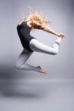 The dancer. Beautiful ballet dancer jumping on grey background Stock Photography
