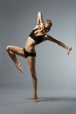 The dancer. Ballet dancer posing on grey Royalty Free Stock Photography
