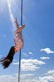 Dancer acrobatic performance on pole with smile in summer sun Royalty Free Stock Photos