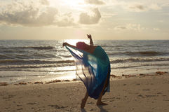 Dancer arching back. An attractive fit blonde dancer is arching back on pointe at the beach in sheer flowing costume looking at you the viewer as the sun begins royalty free stock photo